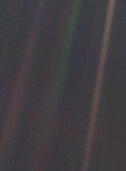 This image shows the Earth as a tiny dot highlighted in a sunbeam. This narrow-angle color image of the Earth, dubbed 'Pale Blue Dot', is a part of the first ever 'portrait' of the solar system taken by Voyager 1. The spacecraft acquired a total of 60 frames for a mosaic of the solar system from a distance of more than 4 billion miles from Earth and about 32 degrees above the ecliptic. From Voyager's great distance Earth is a mere point of light, less than the size of a picture element even in the narrow-angle camera. Earth was a crescent only 0.12 pixel in size. Coincidentally, Earth lies right in the centre of one of the scattered light rays resulting from taking the image so close to the sun. This blown-up image of the Earth was taken through three color filters – violet, blue and green – and recombined to produce the color image. The background features in the image are artifacts resulting from the magnification.
